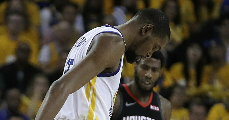The Golden State Warriors' Kevin Durant limps off the court.