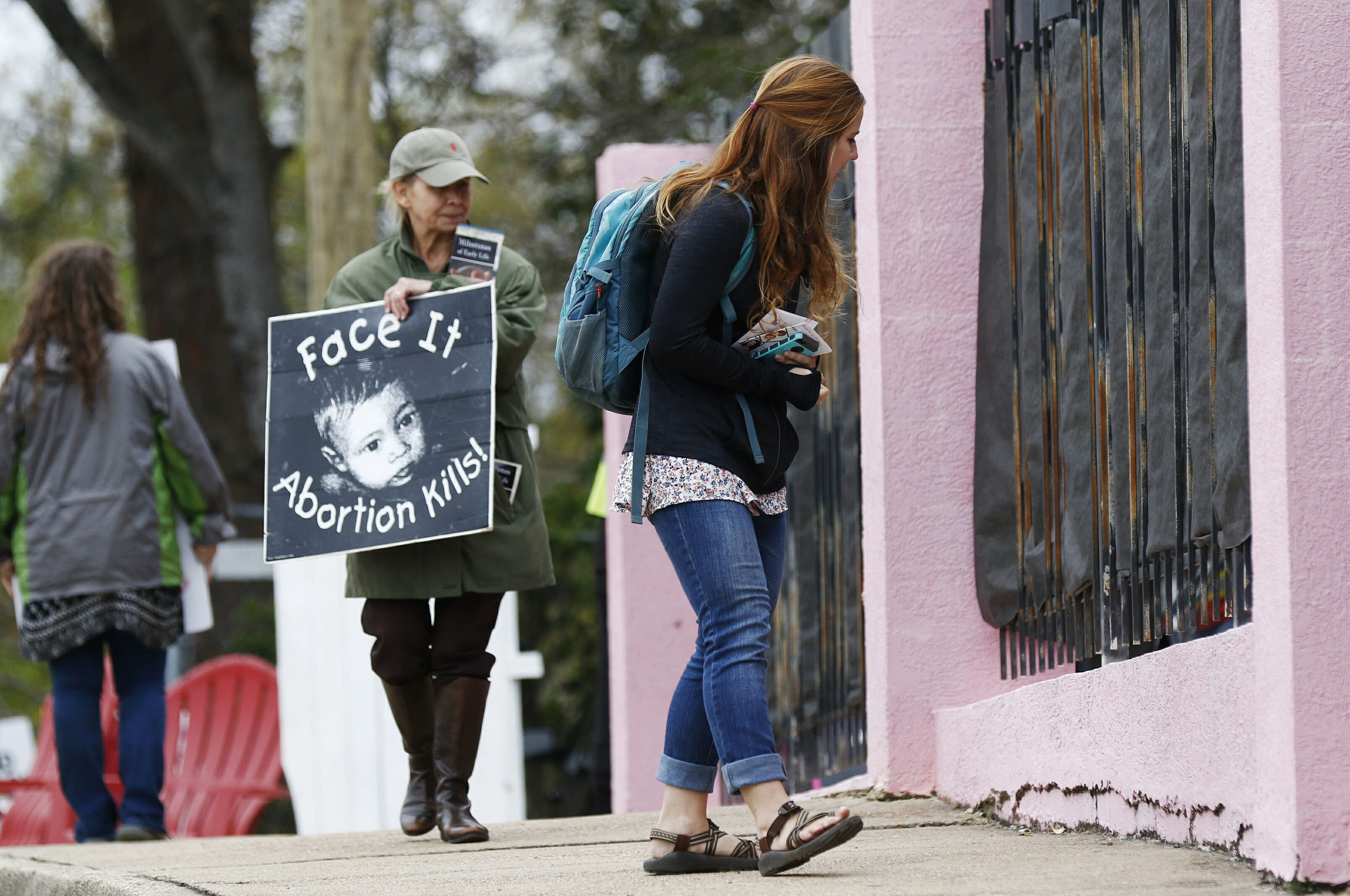 In this March 20, 2018, file photo, anti-abortion sidewalk counselors call out to a woman entering the Jackson Women's Health Organization's clinic, the only facility in the state that performs abortions, in Jackson, Mississippi.
