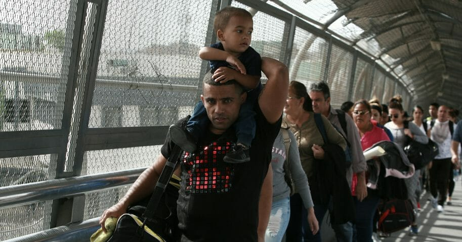 Cuban migrants escorted by Mexican immigration officials in Ciudad Juarez, Mexico, as they cross the Paso del Norte International Bridge on April 29, 2019.