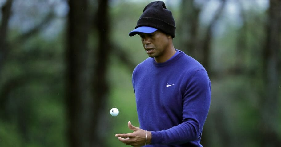 Tiger Woods, wearing cold weather gear, flips his ball.