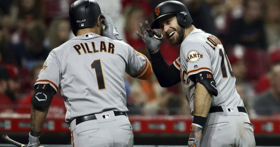 San Francisco Giants' Evan Longoria celebrates with Kevin Pillar after hitting a home run for the go-ahead run in the 11th inning against the Cincinnati Reds on Friday, May 3, 2019, in Cincinnati.