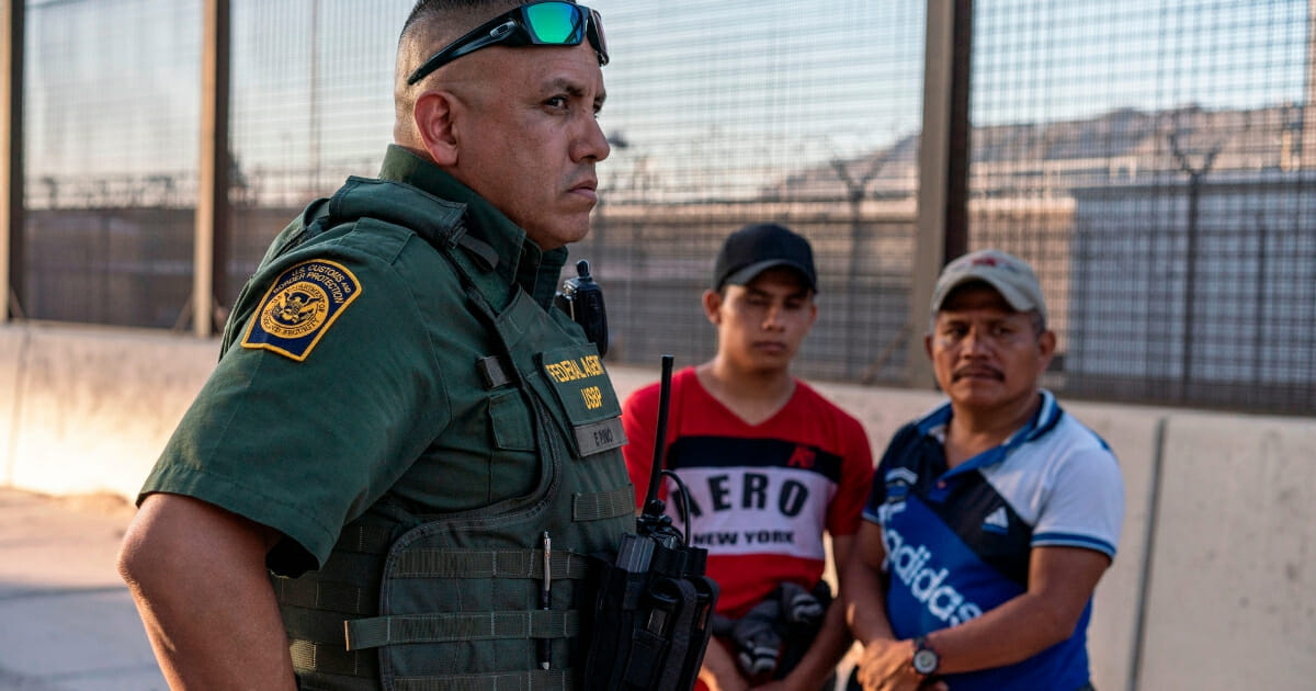 Border Patrol agent Frank Pino, left, is pictured with two migrants who presented themselves to the Border Patrol in El Paso, Texas on May 16, 2019. (PAUL RATJE / AFP / Getty Images)
