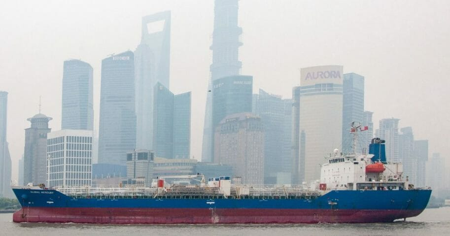 A cargo ship sails past skyscrapers of Shanghai in June 2013.