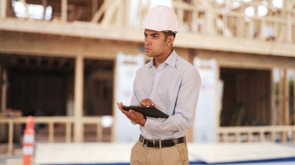 Millennial Latino architect contractor on construction site wearing hard hat