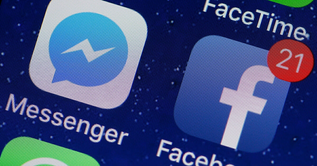 In this photo illustration, the logo of the Messenger and Facebook applications are displayed on the screen of an Apple iPhone on April 6, 2018 in Paris. (Photo Illustration by Chesnot / Getty Images)