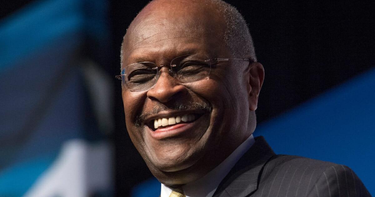Herman Cain smiles.