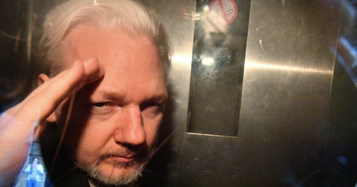 WikiLeaks founder Julian Assange gestures from the window of a prison in Southwark Crown Court in London on May 1, 2019.