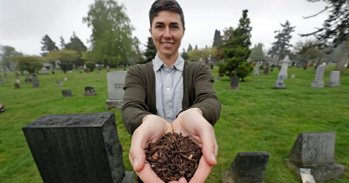 In this April 19, 2019, file photo, Katrina Spade, the founder and CEO of Recompose, a company that hopes to use composting as an alternative to burying or cremating human remains, poses for a photo in a cemetery in Seattle, as she displays a sample of compost material left from the decomposition of a cow using a combination of wood chips, alfalfa and straw. (Elaine Thompson / AP Photo)