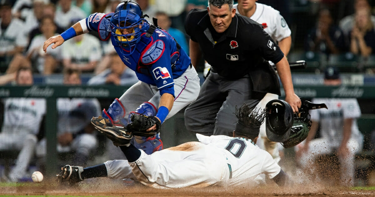 Mallex Smith of the Seattle Mariners slides home against the Texas Rangers.