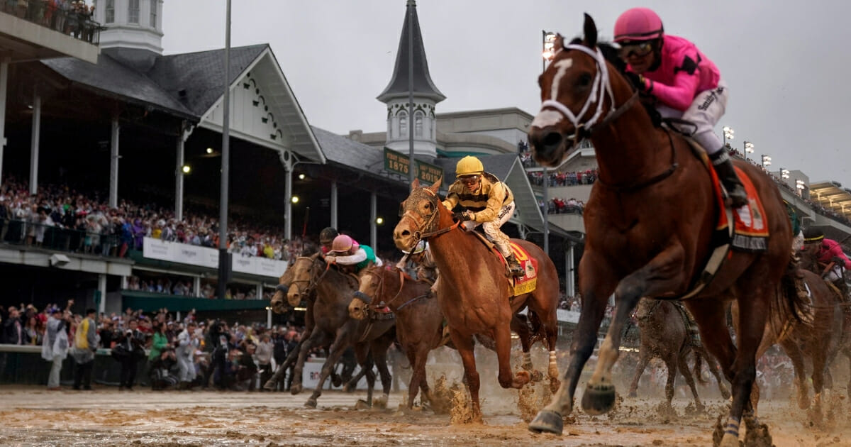 Luis Saez rides Maximum Security, right, across the finish line first in the 145th Kentucky Derby.