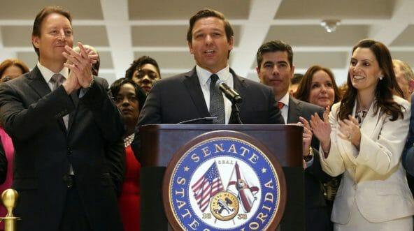 Ron DeSantis surrounded by legislators clapping