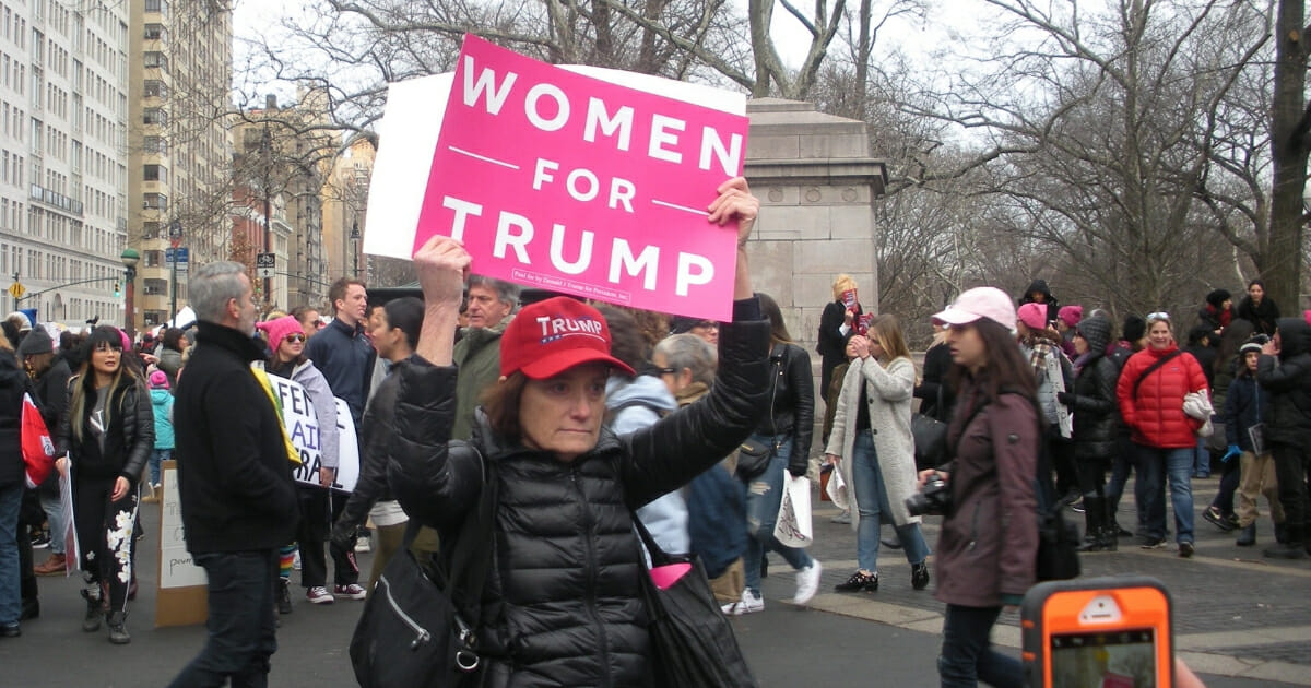 """A Trump supporter at that Women's March in New York City holds a pink sign that says, """"Women for Trump"""""""