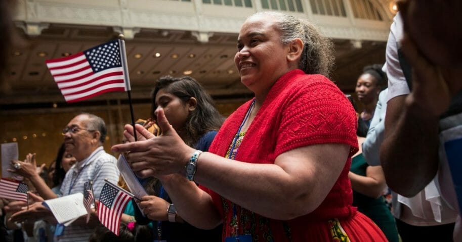 New U.S. citizens cheer after reciting the Oath of Allegiance during naturalization ceremony at the New York Public Library.