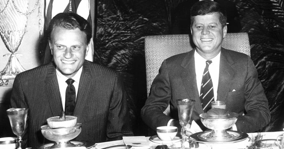 Christian evangelist Billy Graham, left, sits with former President John F. Kennedy, right. at the National Prayer Breakfast in Washington, D.C, on Feb. 9, 1994.