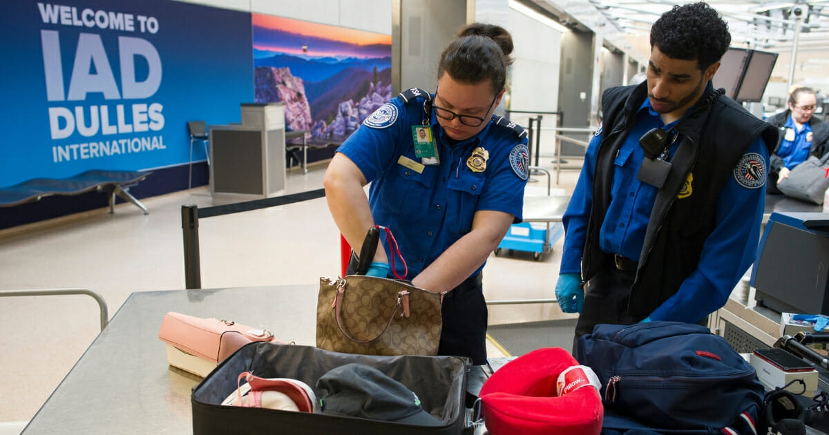 Transportation Security Administration officers search handbags which were packed in a suitcase at a checkpoint at Dulles International Airport in Dulles, Virginia on March 26, 2019.