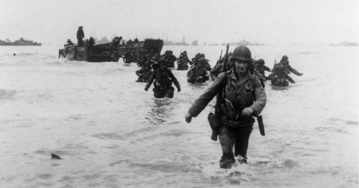 American soldiers strid through the Normandy waves.
