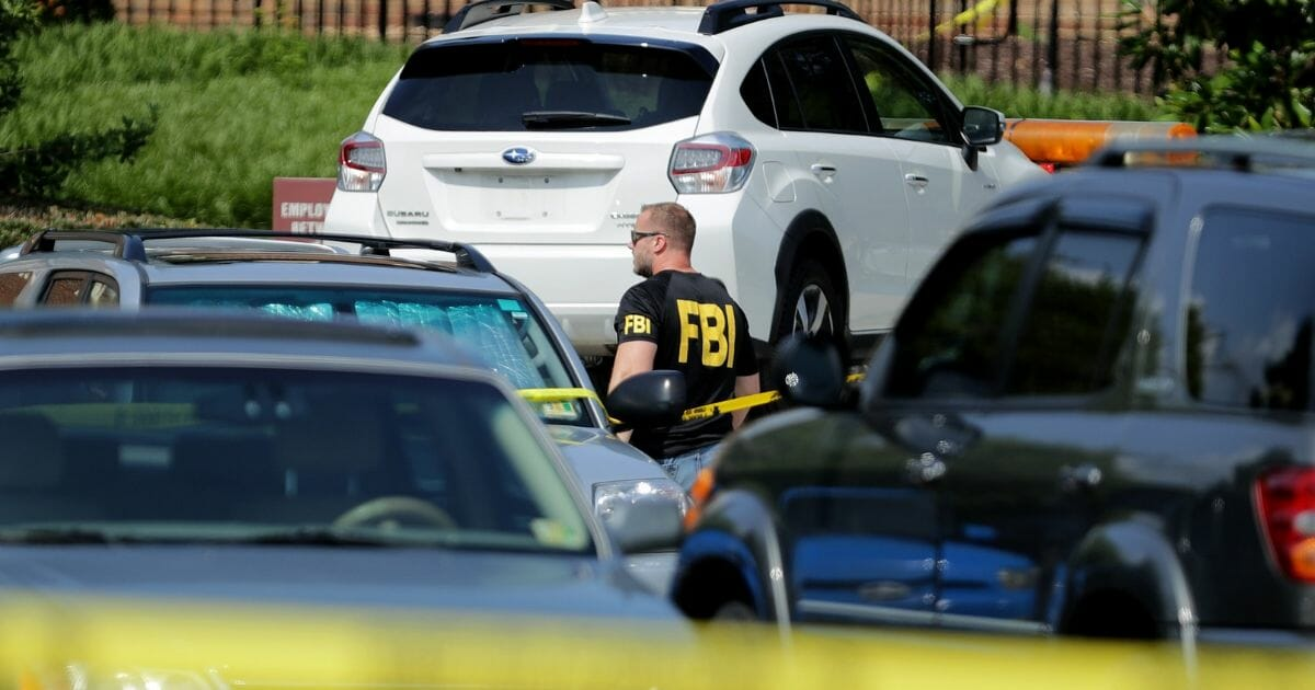 An FBI agent watches as a vehicle is towed from the scene of the May 31 mass shooting in Virginia Beach, Virginia.