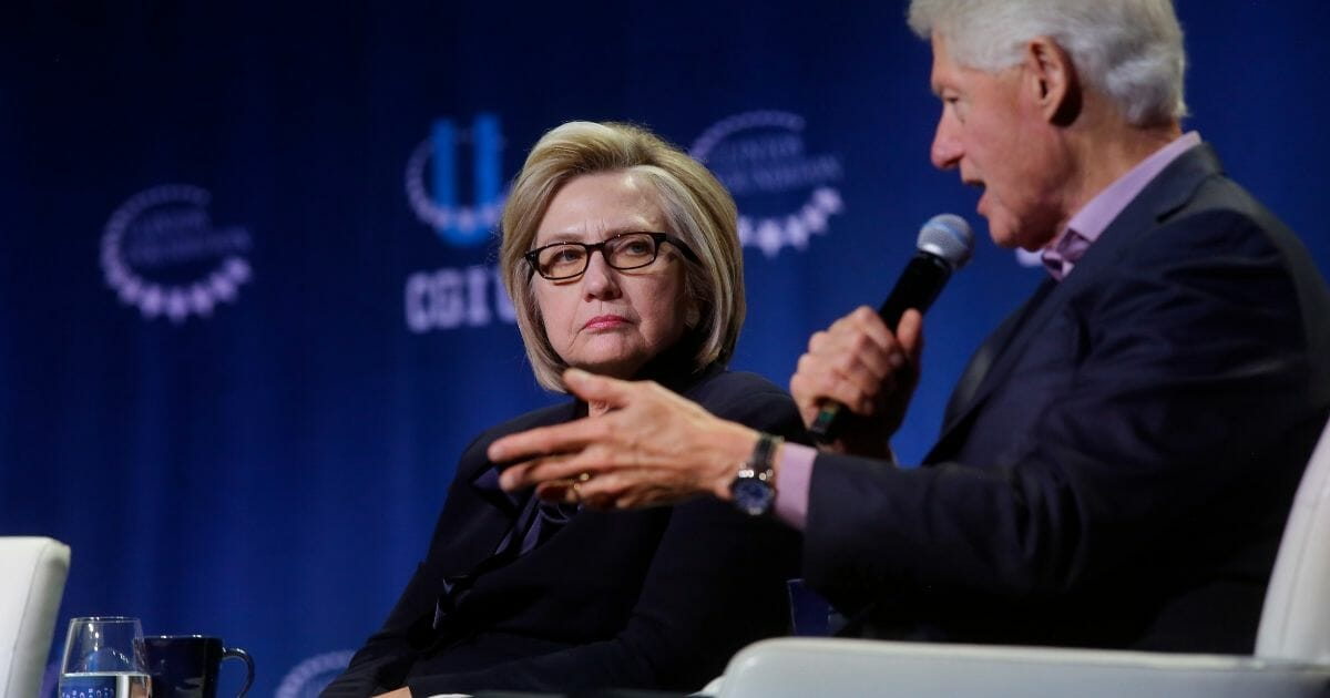 Hillary and Bill Clinton onstage, with Hillary not looking happy.