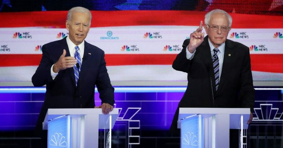 Democratic presidential candidates former Vice President Joe Biden and Sen. Bernie Sanders speak during the second night of the first Democratic presidential debate on June 27, 2019 in Miami, Florida.