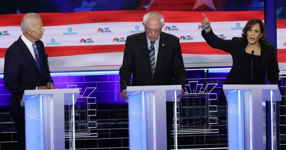 Sen. Kamala Harris speaks as Sen. Bernie Sanders (C) and former Vice President Joe Biden look on during the second night of the first Democratic presidential debate on June 27, 2019 in Miami, Florida.