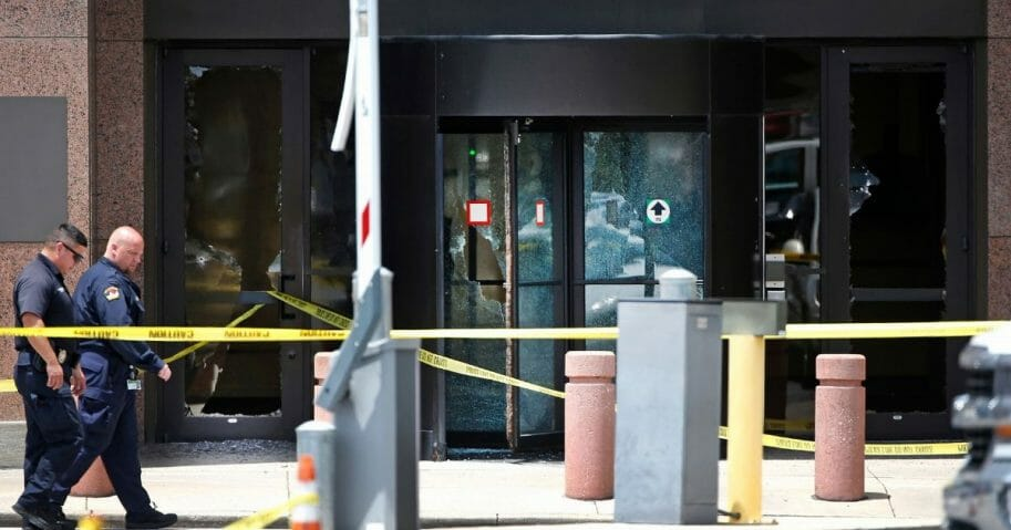 Dallas police walk past the bullet riddled glass doors of the Earle Cabell Federal Building on June 17, 2019.