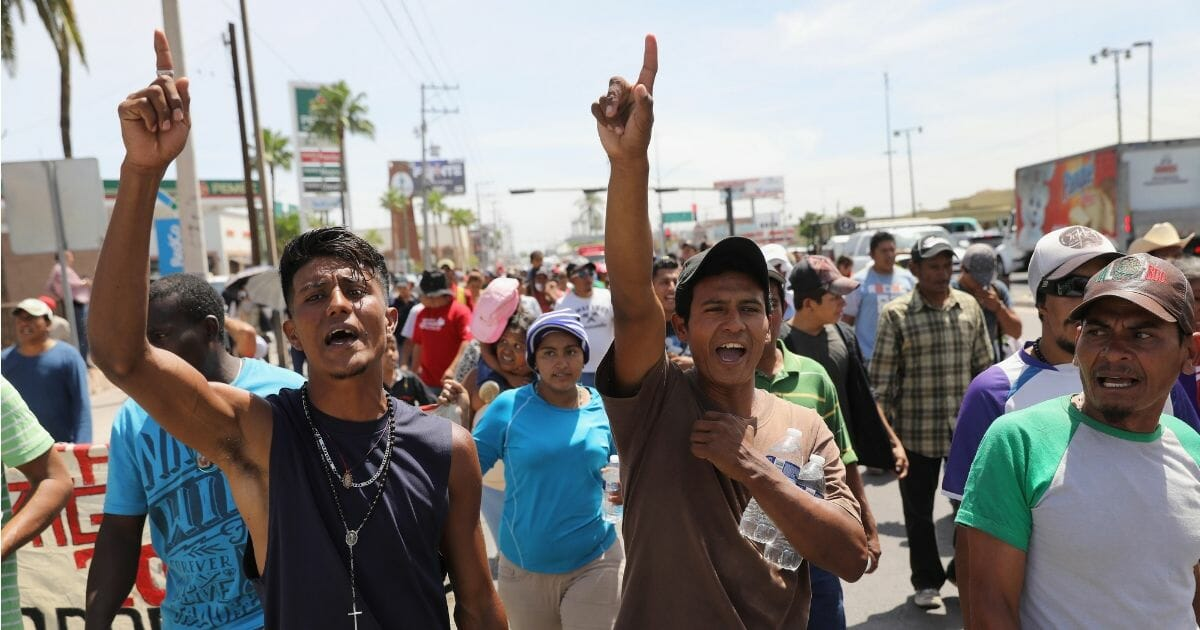 """Central American immigrants, part of an immigrant """"caravan,"""" march in protest against U.S. President Donald Trump."""