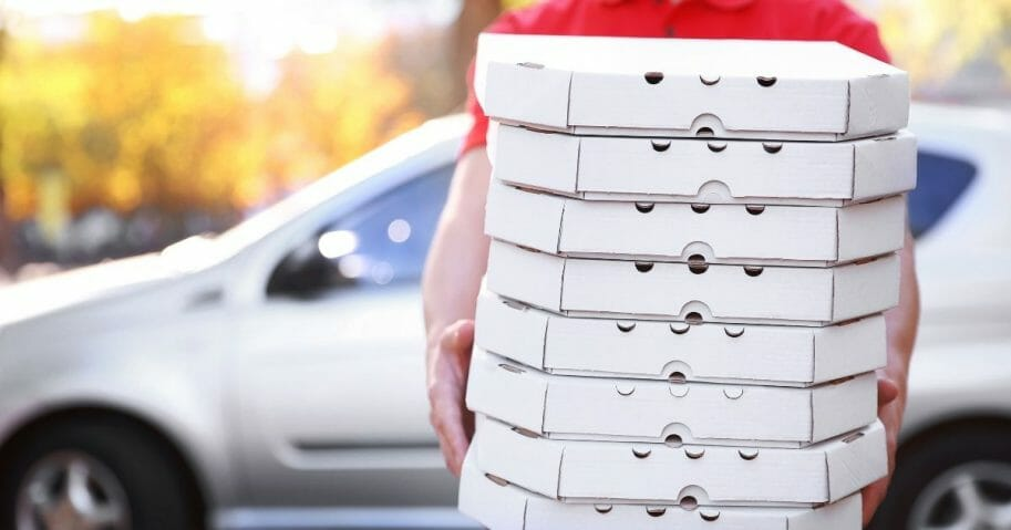Pizza delivery boy holding boxes of pizza
