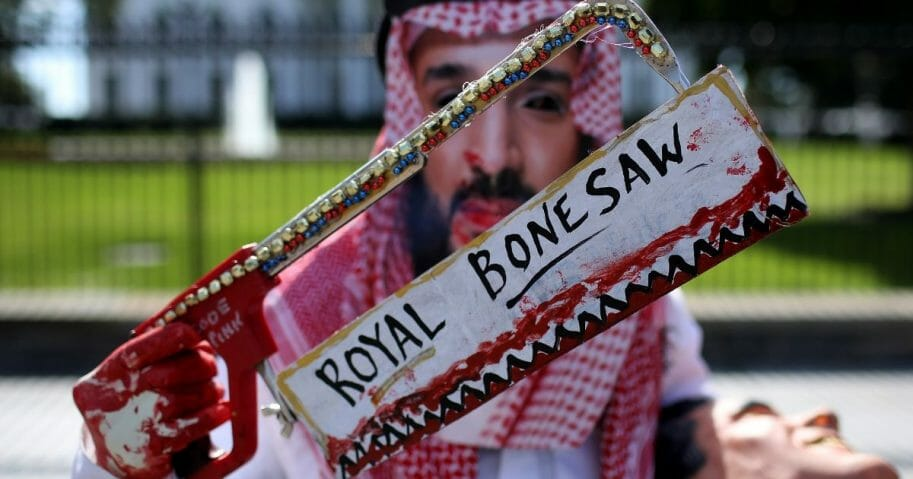 A protester dressed as Saudi Arabian crown prince Mohammad bin Salman, demonstrates with members of the group Code Pink outside the White House in the wake of the disappearance of Saudi Arabian journalist Jamal Khashoggi October 19, 2018.