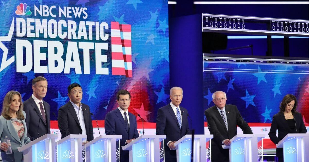 Democratic 2020 presidential candidates listen to a question June 27, 2019, in Miami, Fla.