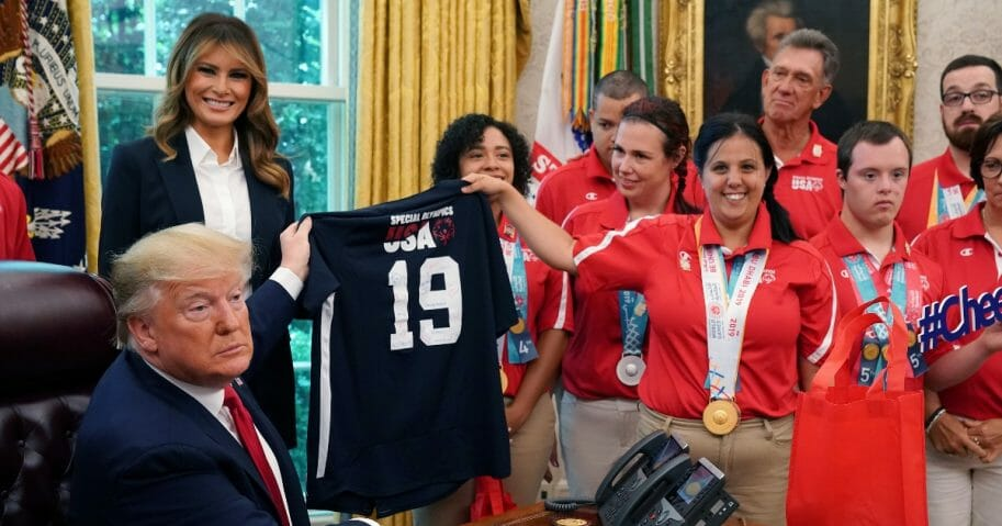 President Donald Trump, left, accepts a jersey from members of the United States Special Olympics World Games team while he and first lady Melania Trump host them in the Oval Office at the White House July 18, 2019 in Washington, D.C.