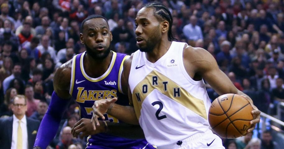 Kawhi Leonard of the Toronto Raptors dribbles as LeBron James of the Los Angeles Lakers defends.