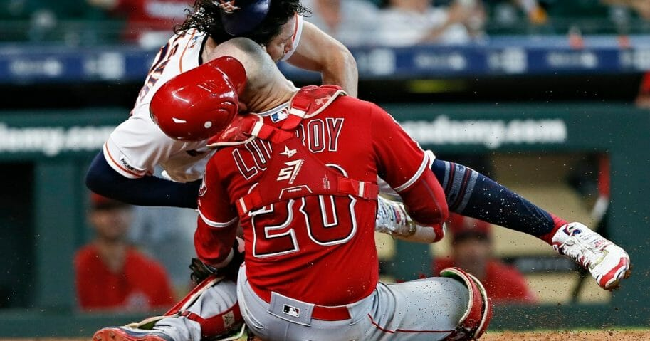 Jake Marisnick of the Houston Astros collides with catcher Jonathan Lucroy of the Los Angeles Angels as he attempts to score in the eighth inning at Minute Maid Park on July 7, 2019