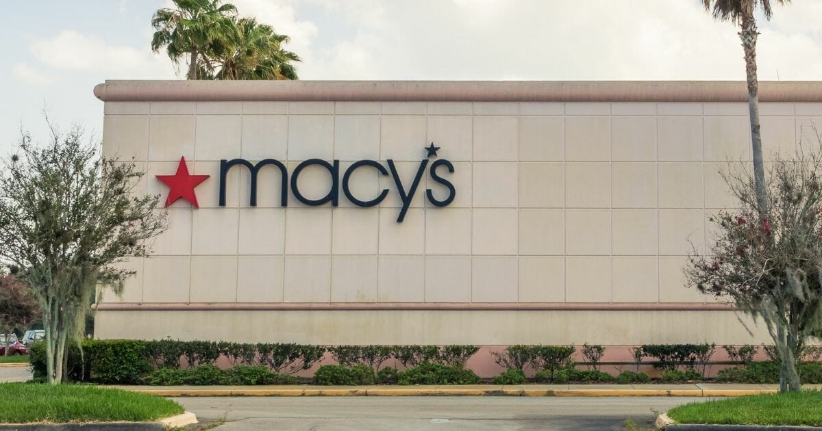 Macy's store logo is pictured on the outside of the store a long with tall palm trees on a sunny day in Florida.