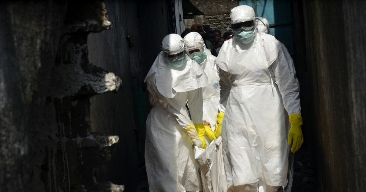 Red cross workers, wearing protective suits, carry the body of a person who died from Ebola during a burial with relatives of the victims of the virus, in Monrovia, on Jan. 5, 2015.