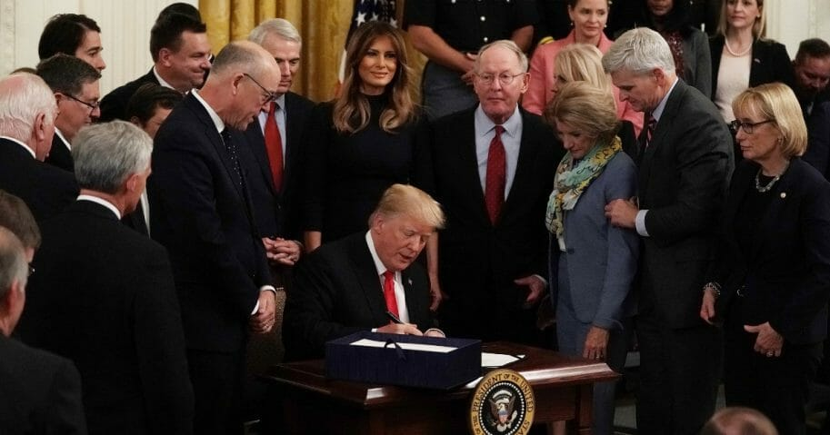 Flanked by lawmakers and first lady Melania Trump, President Donald Trump signs a bill to dedicate more resources to fight the opioid crisis during an Oct. 24, 2018, ceremony in the East Room of the White House.