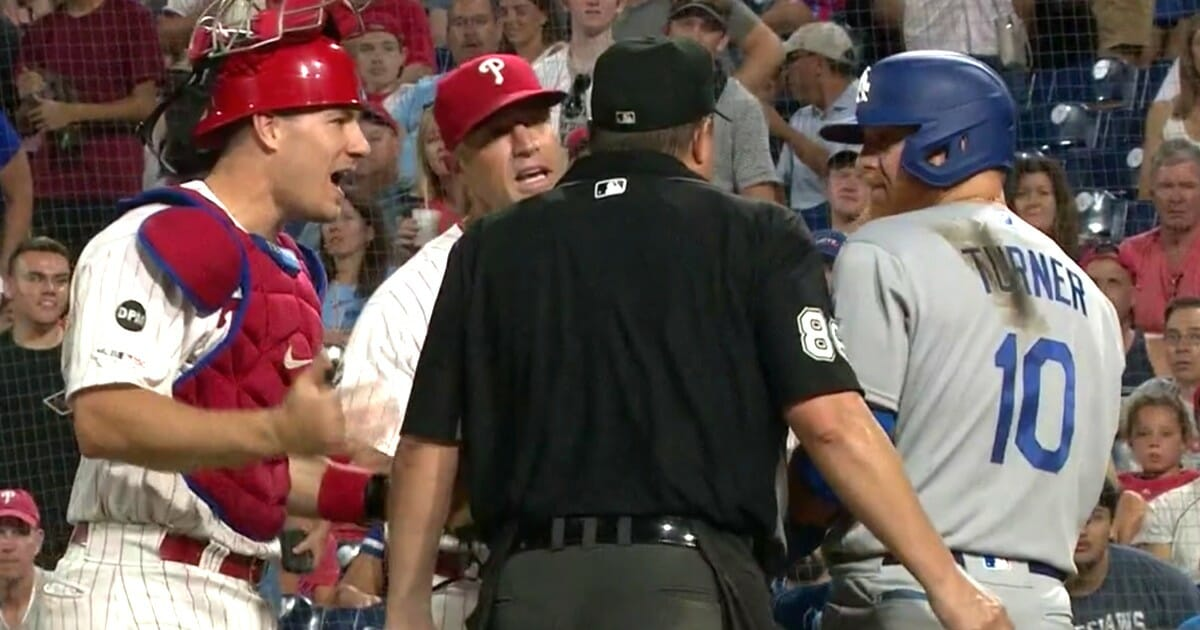 The Los Angeles Dodgers' Justin Turner joins the Phillies in arguing against the ejection of Philadelphia pitcher Yacksel Ríos, who had just plunked him on the knee.