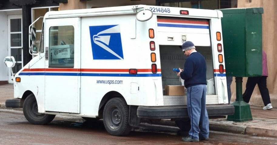 A U.S. postal worker delivers mail and packages in Santa Fe, New Mexico
