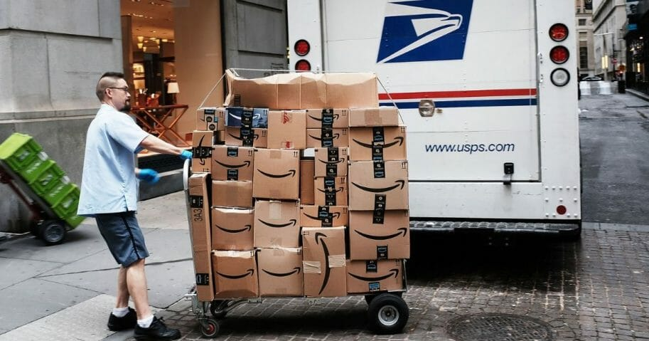 A US Postal worker delivers Amazon boxes outside of the New York Stock Exchange.