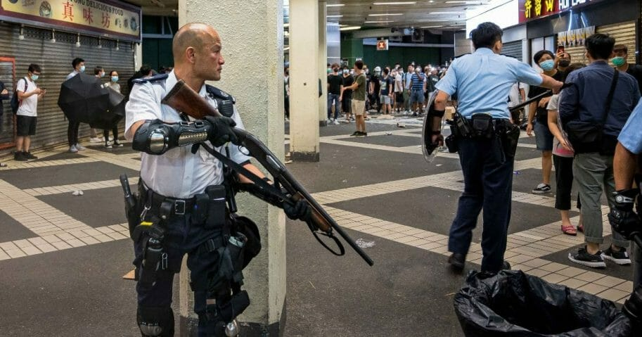 Armed riot cop squares off against Hong Kong protesters.