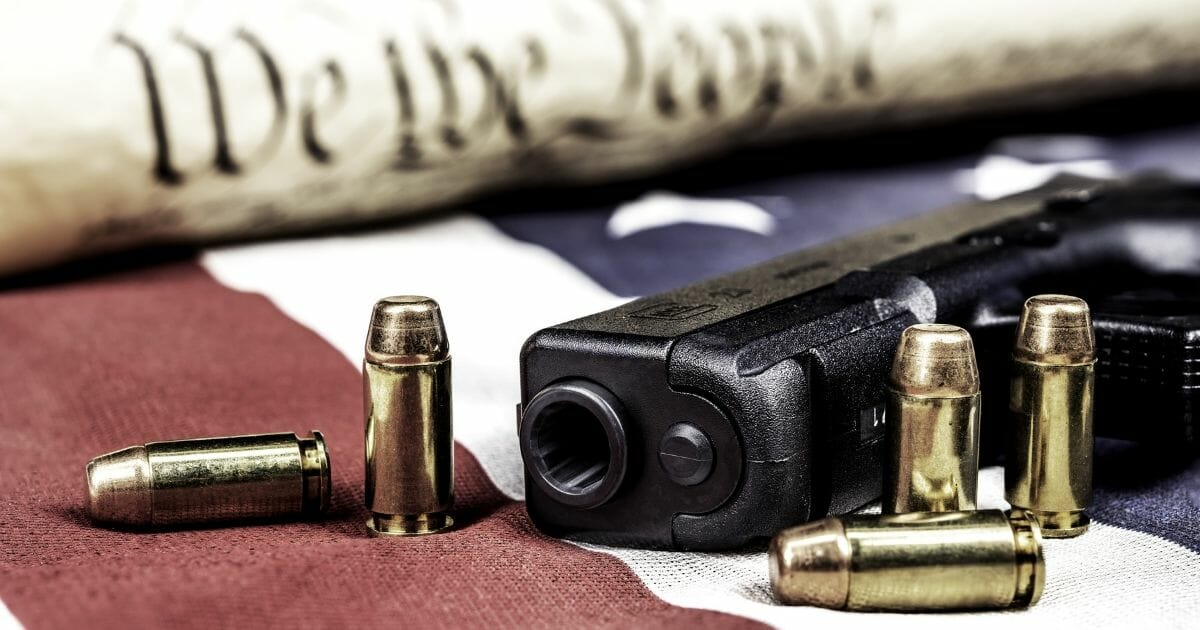 Gun with flag and copy of the Constitution.