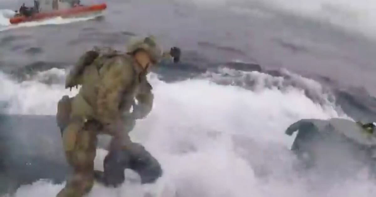 A U.S. Coast guardsman boards a moving submersible in a drug intervention