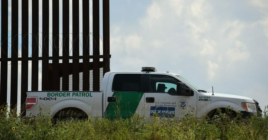 A border patrol truck near a fence on the U.S.-Mexico border