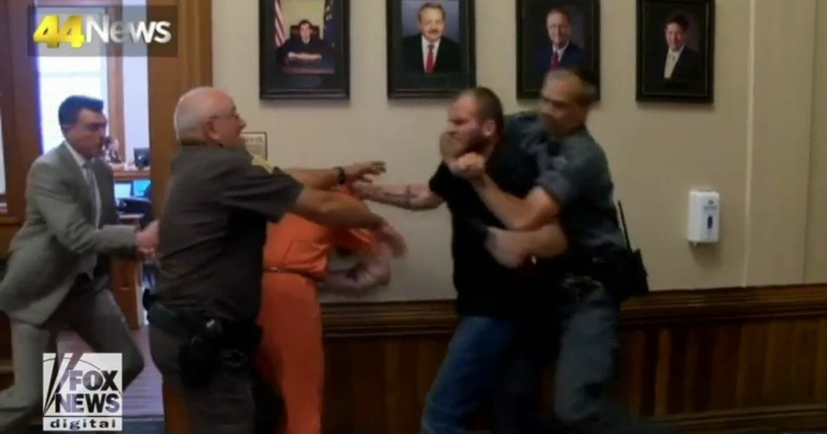 Jeremiah Hartley, second from right, punches Kwin Boes, third from left, in an Indiana courthouse