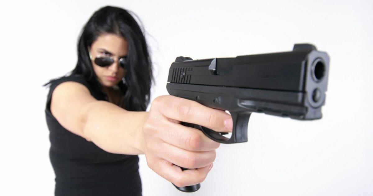 A woman takes aim with a handgun.