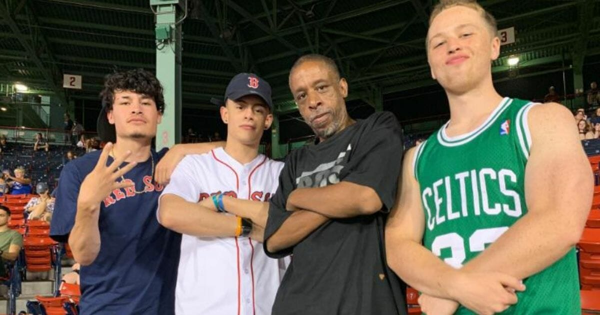 three young men and one older man pose at a MLB game