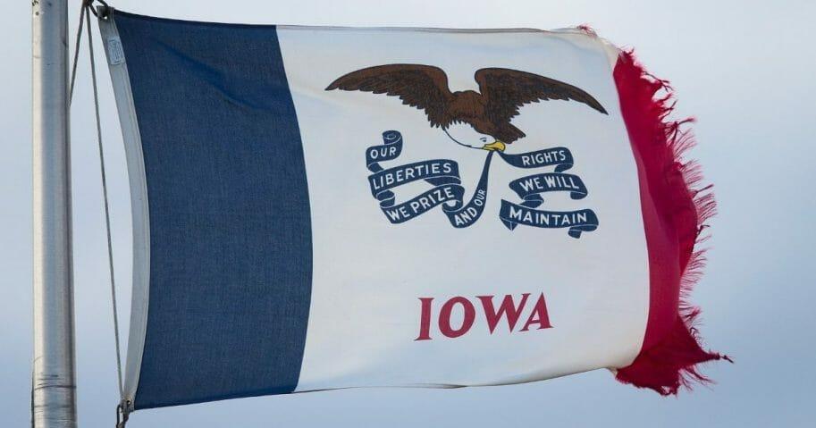 An Iowa state flag flies near the entrance to a farm