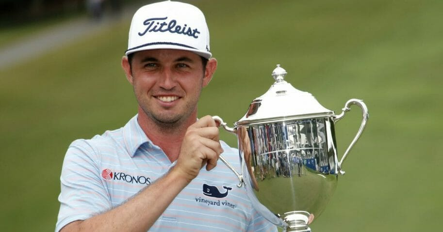 J. T. Poston holds the trophy after he won the Wyndham Championship
