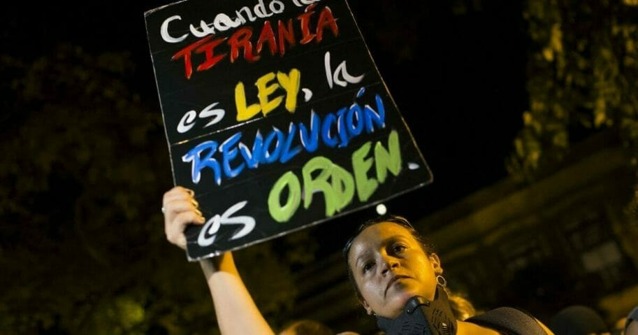 """A woman holds a sign with message that reads in Spanish: """"When tyranny is the law, a revolution is in order"""" during a protest outside the governor's residence, the Fortaleza, after Pedro Pierluisi was sworn in as Puerto Rico's governor, in San Juan, Puerto Rico, Friday, Aug. 2, 2019."""