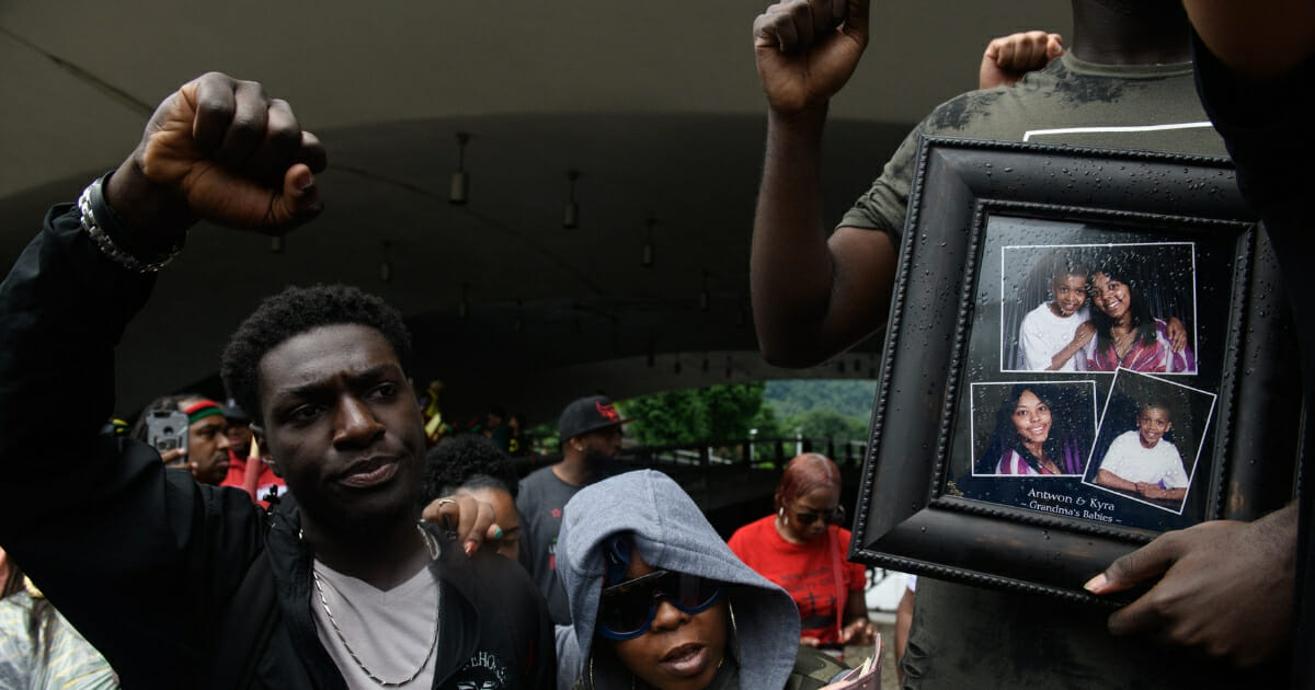 A man holds a photo of Antwon Rose, who was fatally shot by a police officer, during a protest June 23, 2018, in Pittsburgh.