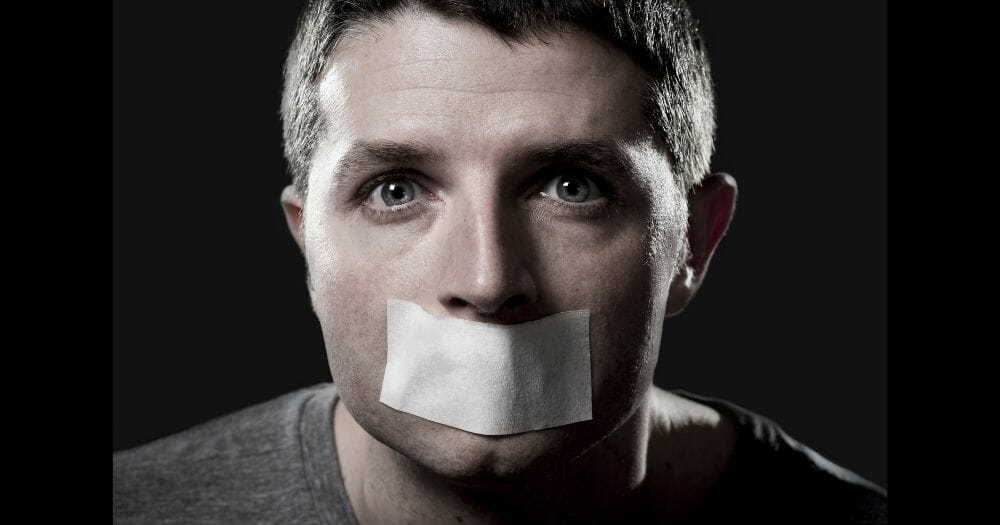 attractive young man with mouth and lips sealed on tape to prevent from speaking free keeping him mute and censored in freedom of speech and expression concept close up eyes isolated on black - Image